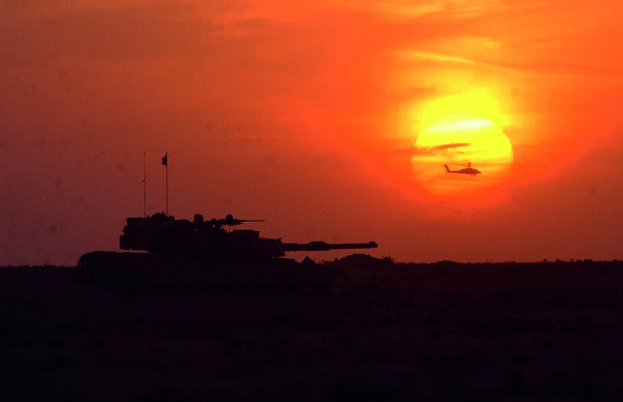 The US Army M1AI Abrams tank sits in the frontline while an AH-64D Apache attack helicopter flies in front of the sunsetin central Iraq area 01 April 2003 as the 3rd Infantry Division prepares for an offensive.   AFP PHOTO   ROMEO GACAD
